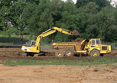 Backhoe unloading dirt from dump truck